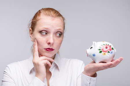 Young thinking red-haired woman holding a piggy bank / porcelain bank in her hand