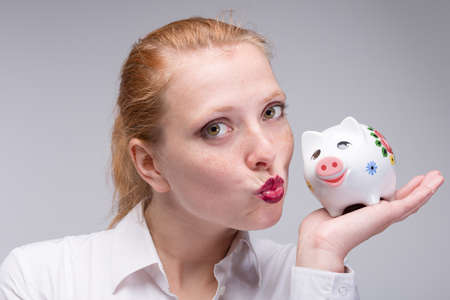 Young happy red-haired woman i sflirting with her piggy bank / porcelain bank in her hand 版權商用圖片