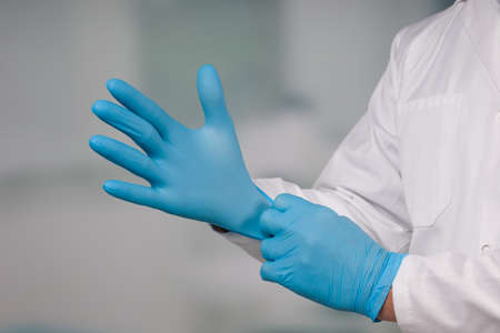 Close up of hands putting on medical gloves for protection 版權商用圖片