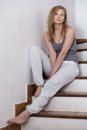 lonely young woman in casual clothes sitting on stairs 版權商用圖片