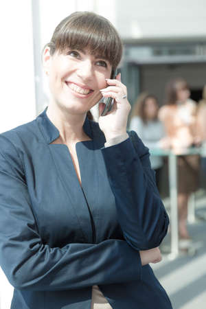 smiling business woman is talking on her phone in front of some collegues