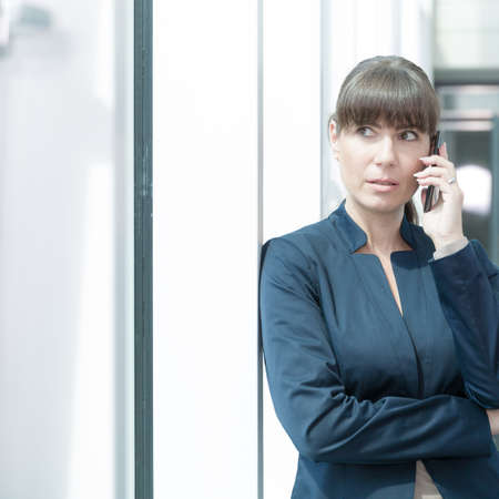 business woman is seriously listening at her phone