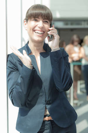 business woman is talking intensely on her phone in front of some collegues