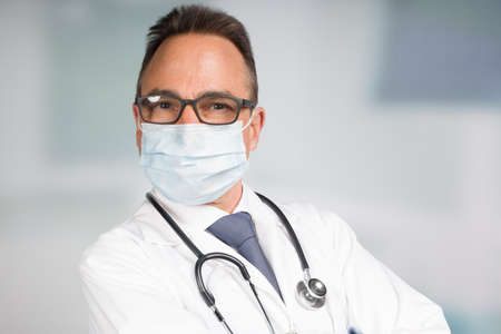 male doctor in lab coat with face mask, medical gloves and stethoscope in front of a clinic room