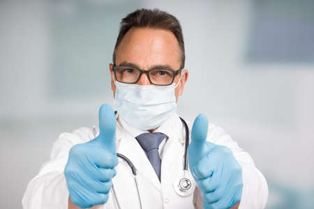 male doctor in lab coat with face mask, medical gloves and stethoscope shows thumbs up