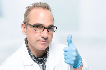 seriously looking male doctor in front of a clinic room shows thumbs up 版權商用圖片