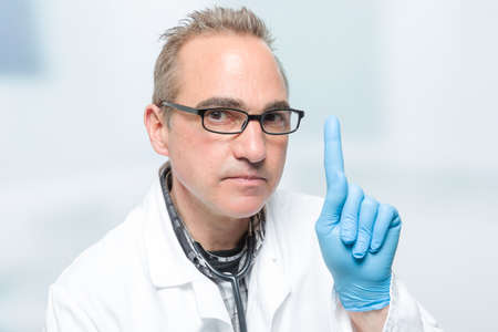 seriously looking male doctor in front of a clinic room is rising his pointer finger