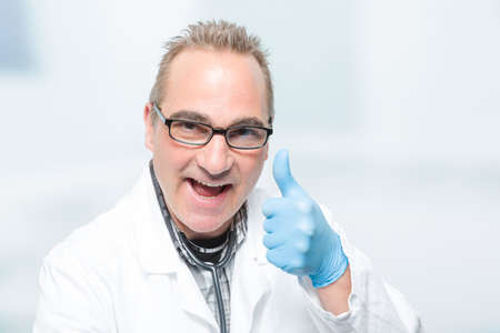 enthusiastic male doctor in front of a clinic room shows thumbs up
