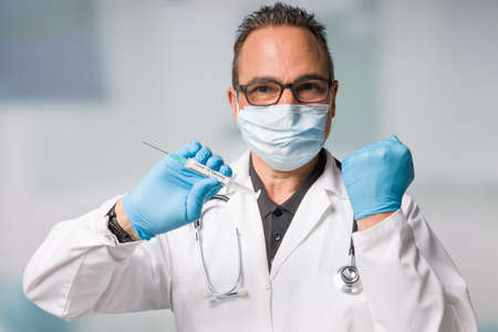 doctor with medical face mask and medical gloves presenting a syringe pulled up with a coronavirus vaccine and doing a success gesture