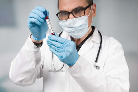 doctor or scientist is handling a positive   antibody test tube 版權商用圖片