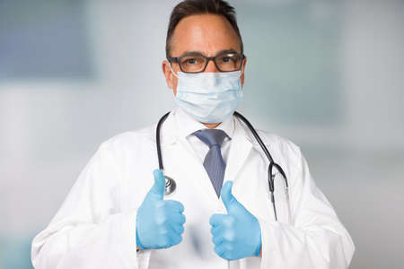 doctor in lab coat with medical face mask and medical gloves shows thumbs up