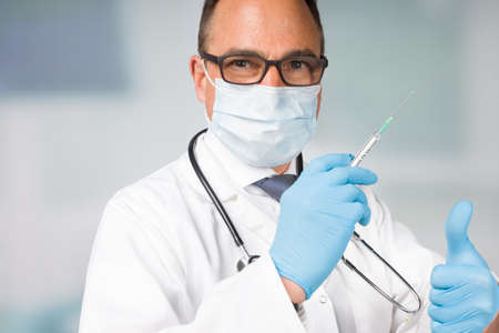 doctor with medical face mask and medical gloves presenting a syringe pulled up with a vaccine 版權商用圖片
