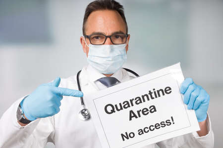 Doctor with medical face mask and medical gloves is pointing to a quarantine sign in front of a restricted area