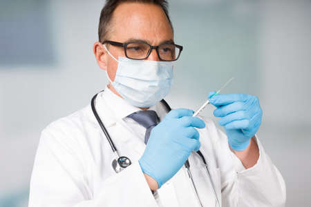 doctor with medical face mask and medical gloves presenting a syringe pulled up with a coronavirus vaccine