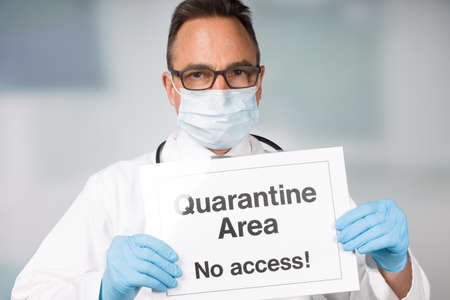 Doctor with medical face mask and medical gloves showing quarantine sign in front of a restricted area