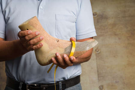 Close up of hands of an orthopedic shoemaker presenting an individual crafted wooden last 版權商用圖片