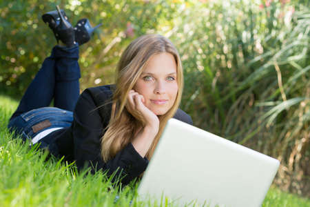 woman in business outfit is working happily outdoor at her laptop