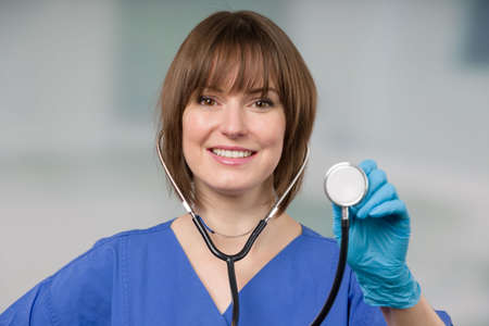 friendly female doctor or nurse with a stethoscope and blue gloves in front of a clinic room 版權商用圖片