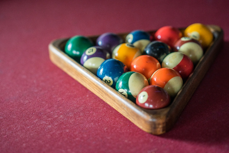 snooker halls: Colorful vintage billiard balls in a burgundy pool table Stock Photo