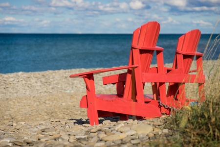 Red Muskoka Chairs on the banks of the Georgian Bay. Patio furniture overlooking the Great Lakes during a beautiful calm summer day. Relaxing on vacation, Canada Day.