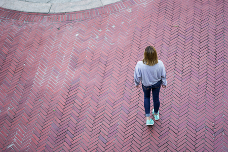 Young blonde woman standing or walking in a city square, brick pattern on the floor. Wearing jeans, a sweater and running shoes. Looking down from a high vantage point. Stock Photo