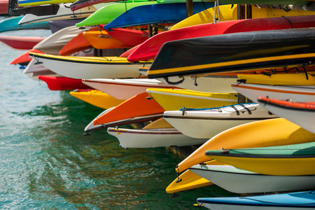 Colorful canoes and kayaks by the lake on a sunny day. Used for summer boating and recreational sport activities on water.