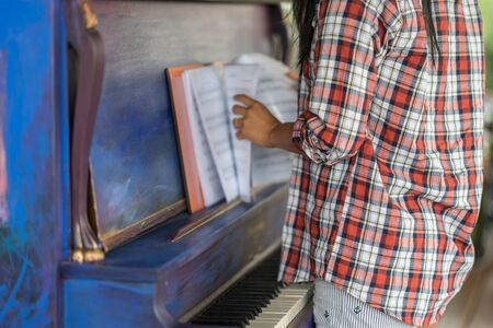 Portrait of a young female flipping through sheet music on a vintage painted colorful piano and black and white keys. Artistic blue and purple brush strokes, classical music instrument.
