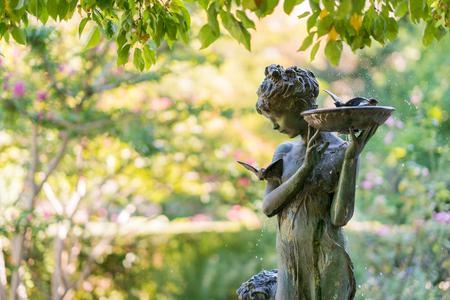 Sculpture of a girl with a bird bath, fountain. Natural setting with a bronze fountain statue in a garden, New York Stock Photo