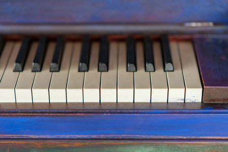 Vintage painted colorful piano and black and white keys. Artistic blue and purple brush strokes, classical music instrument. Stock Photo