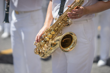 Saxophone player in a military or marching band playing during a parade or festival on a sunny day. Wearing a white uniform with the brass instrument shining gold in the sun. Stock Photo