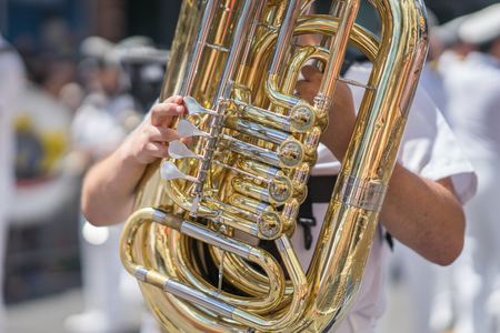 Tuba player in a military or marching band playing during a parade or festival on a sunny day. Wearing a white uniform with the brass instrument shining gold in the sun.