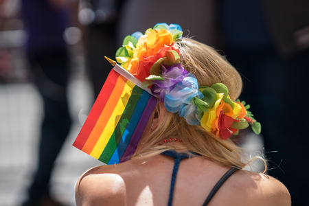 Young blonde woman in a crowd celebrating Pride Parade. Wearing colorful rainbow accessories and a flower crown and a rainbow flag. During a march supporting marriage equality and LGBT rights. Stock Photo