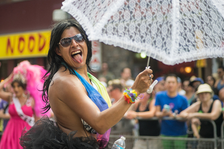 June 29, 2014, Toronto, Canada. Performer marching in the Toronto Pride Parade wearing rainbow flag. Caring a lace umbrella with a cheerful expression. Supporting marriage equality and LGBT rights.