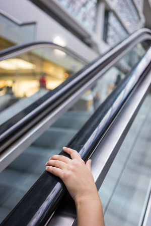 One hand visible in the frame holding the escalator rail. Stock Photo