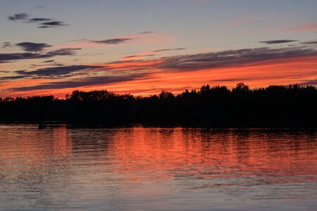 Beautiful summer sunset with a colorful sky and clouds, reflection on the surface of the lake. Relaxing cottage weekend.