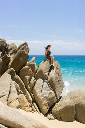 Young woman lounging on the rock formations around the Arch in Cabo San Lucas, Mexico. Interesting shapes of cliffs and stones, beautiful blue water and sunlight. Peaceful vacation spot.