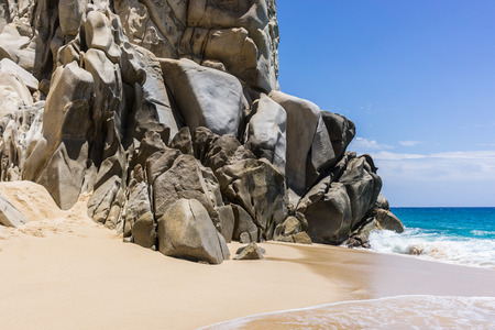 Rock formations and white sandy beach around the Arch in Cabo San Lucas, Mexico. Interesting shapes of cliffs and stones, beautiful blue water and sunlight.