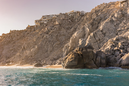 Resort vacation houses and villas nested in the rock formations around the Arch in Cabo San Lucas, Mexico at sunset. Interesting shapes of cliffs and stones, beautiful blue water and sunlight.