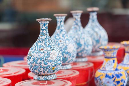 Workshop die geëmailleerde punten zoals kommen, vazen en andere punten van het huisdecor in Peking, China maakt. Schoten van geëmailleerde porseleinverf gemaakt van gepoedercoat glas op metalen oppervlakken.
