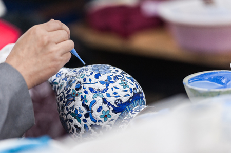 Workshop making enamel items such as bowls, vases and other home decor items in Beijing, China. Shots of porcelain enamel paint made from powdwred glass applied to metal surfaces.