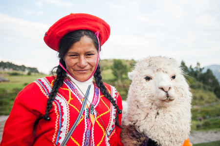 April 22, 2014. Saqsaywaman Ruins near Cusco, Peru. Indigenous woman posing with a llama. She is wearing colorful traditional clothing.