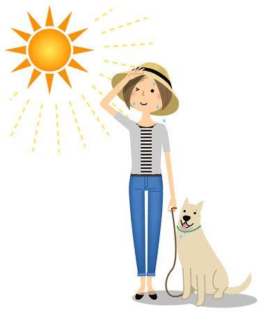 Young woman wearing a hat walking a dog