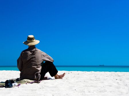 clothed: A fully clothed man sits on a white sand beach on a sunny day, with a ship in the distance