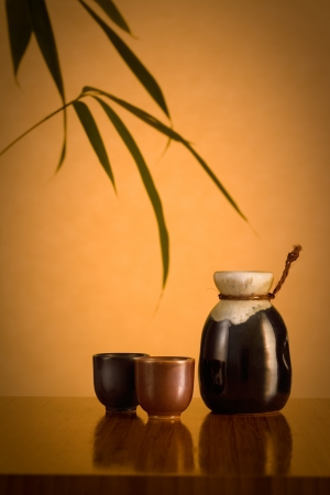 saki: A saki decanter and two cups, on a bamboo table with bamboo leaves in the background  Stock Photo