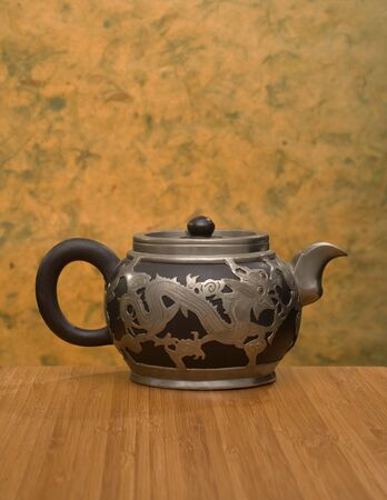A Chinese teapot with dragon motif made of black clay and pewter, circa 1900  Bamboo table with mango leaf paper background  Room for coy  photo