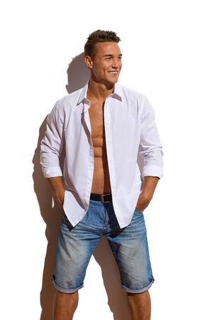 uomini belli: Giovane bello in camicia bianca e jeans sbottonati pantaloncini piedi contro il muro di sole, tenendo le mani in tasca e guardando lontano. Tre quarti lunghezza studio colpo isolato su bianco.
