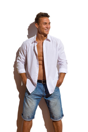 hombres jovenes: joven guapo en camisa desabrochada blanco y pantalones vaqueros de pie contra la pared soleada, con las manos en los bolsillos y mirando a otro lado. Tres cuartos de longitud de tiro del estudio aislado en blanco.