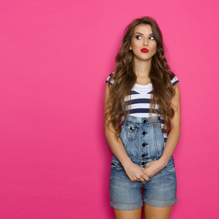 Grimacing young woman in dungarees looking at copy space. Three quarter length studio shot on pink background.