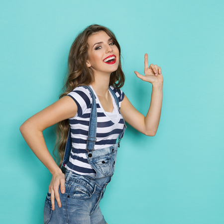 dungarees: Smiling young woman in dungarees and blue striped shirt posing with finger gun. Three quarter length studio shot on teal background. Stock Photo