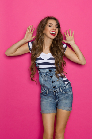 three quarter length: Beautiful young woman in dungarees and stripes shirt shouting with arms raised. Three quarter length studio shot on pink background. Stock Photo